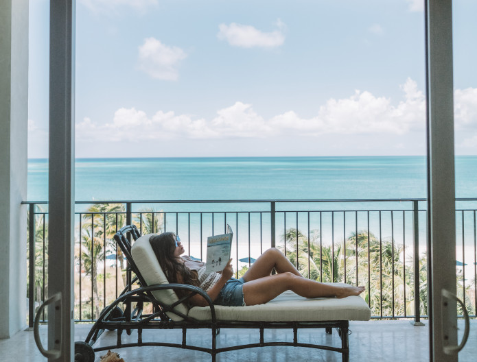 Female on balcony lounge chair reading book
