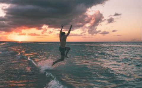 Man jumping into shore at sunset