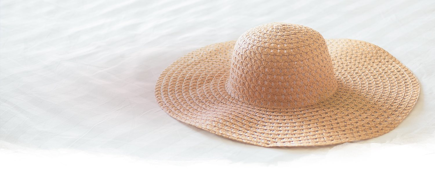 floppy hat sitting on a white linen bed