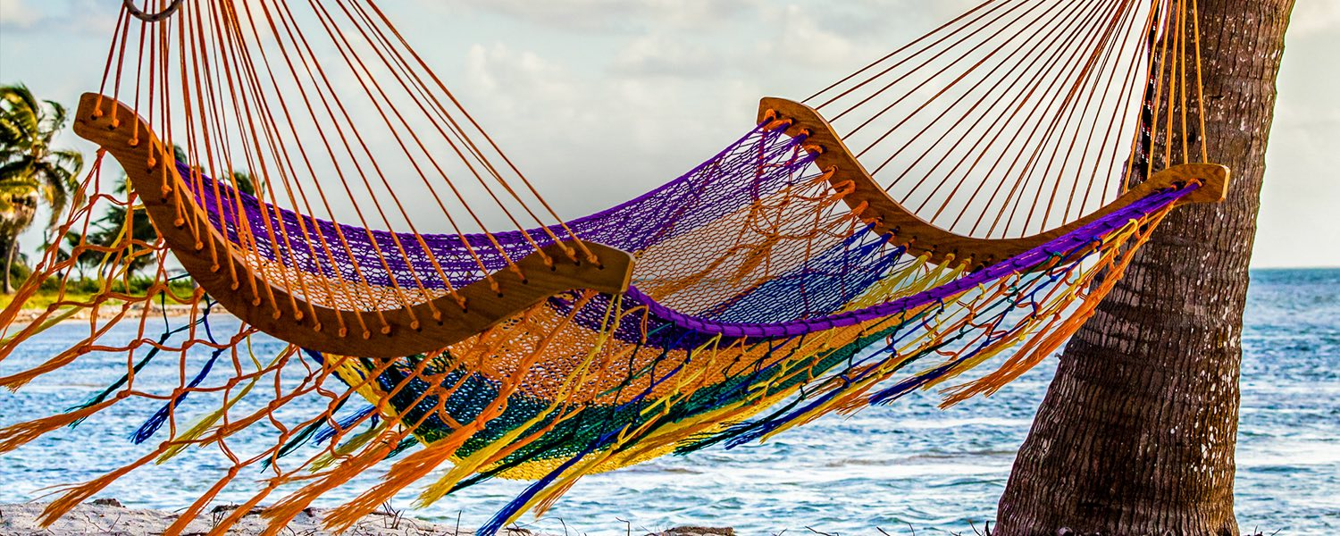 an empty colorful hammock hanging between two palm trees on the beach
