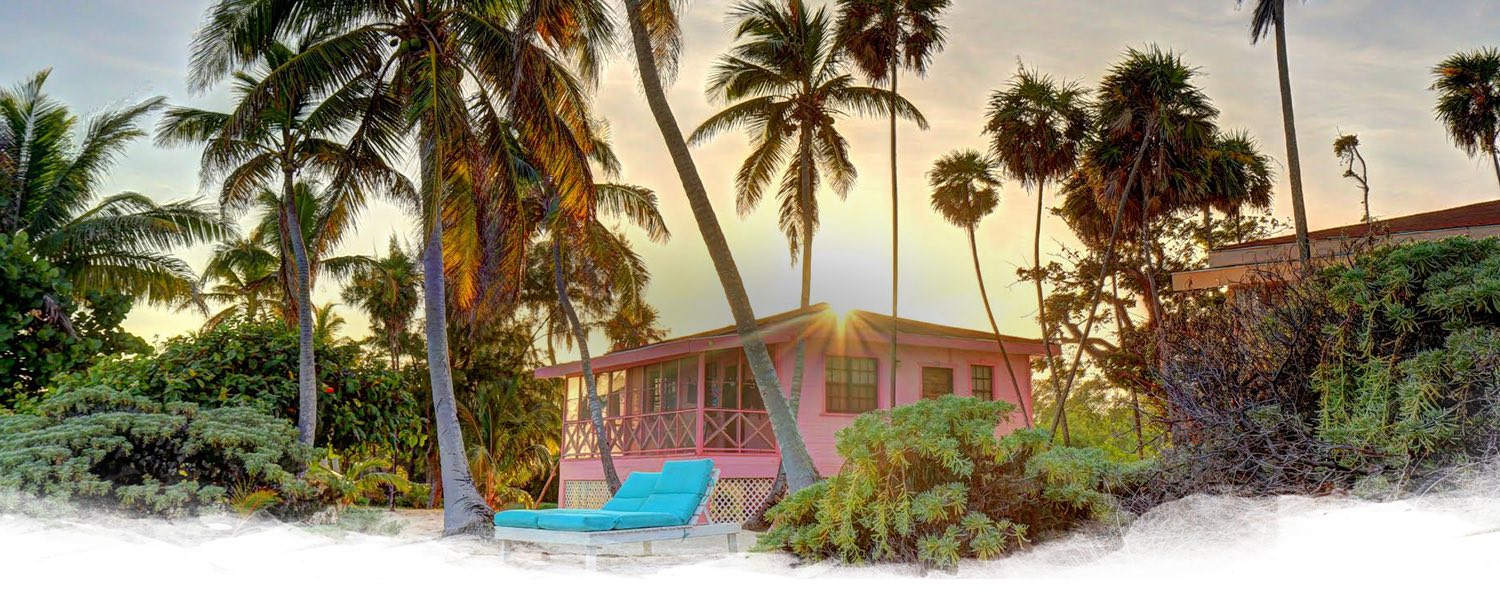 a pink cabana surrounded by greenery and palm trees with the sun glistening behind it