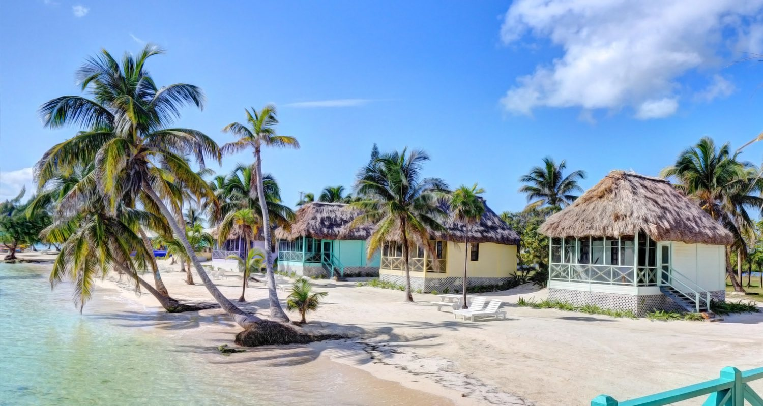 resort cabana houses on the beach with palm trees and calm ocean water