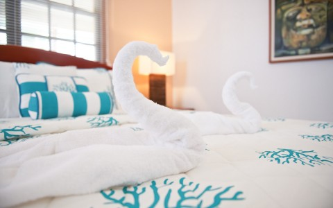 towel folded into a swan sitting on a guest bed