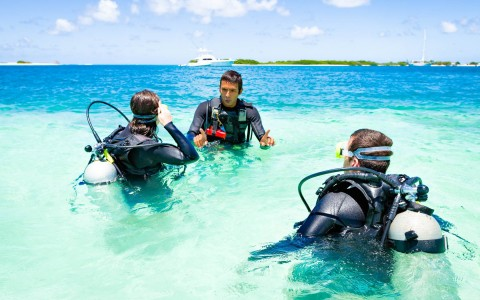 two scuba divers in training standing in ocean water with their instructor