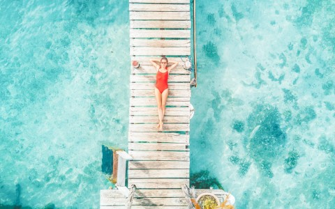 overhead view of a woman in a red swimsuit laying on a dock walkway