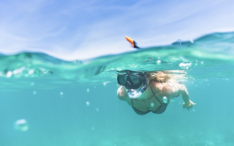 a view of a snorkeler half under water just below the water line