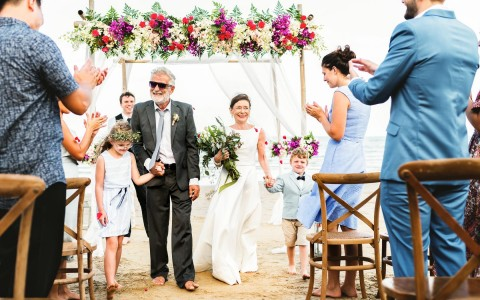 elderly couple holding hands with each other and two small children walking down the isle after renewing their vows at a beach ceremony