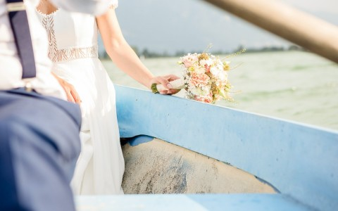 close up of a bride and groom standing together with the ocean in the back