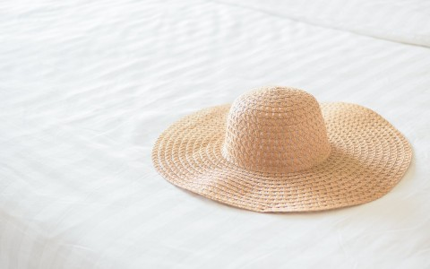 a floppy hat sitting on a white bed
