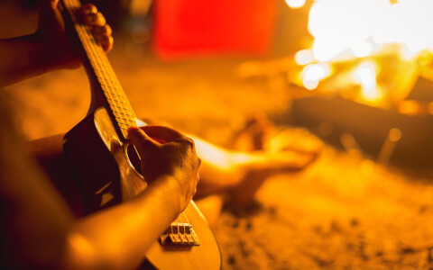 close up of a person playing the guitar while sitting next to a beach bonfire