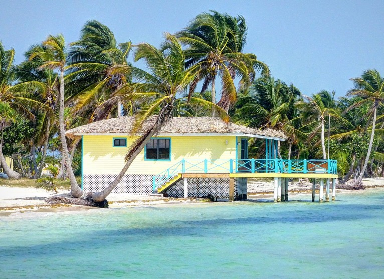 yellow cabana house next to the water with a porch