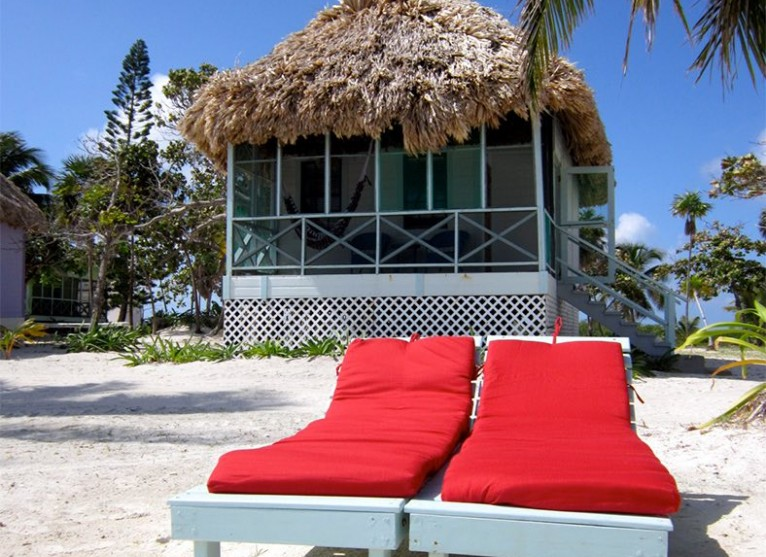 two red cushioned lounge chairs in front of a standard cabana