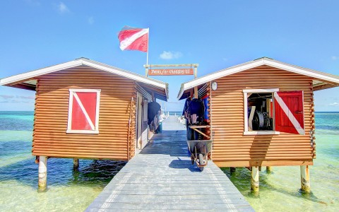 two small buildings off a dock with dive flags