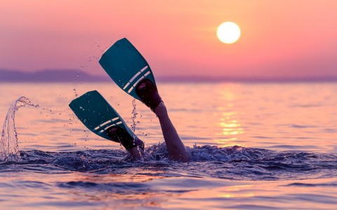 person diving down into the water with only flippers above the water at sunset