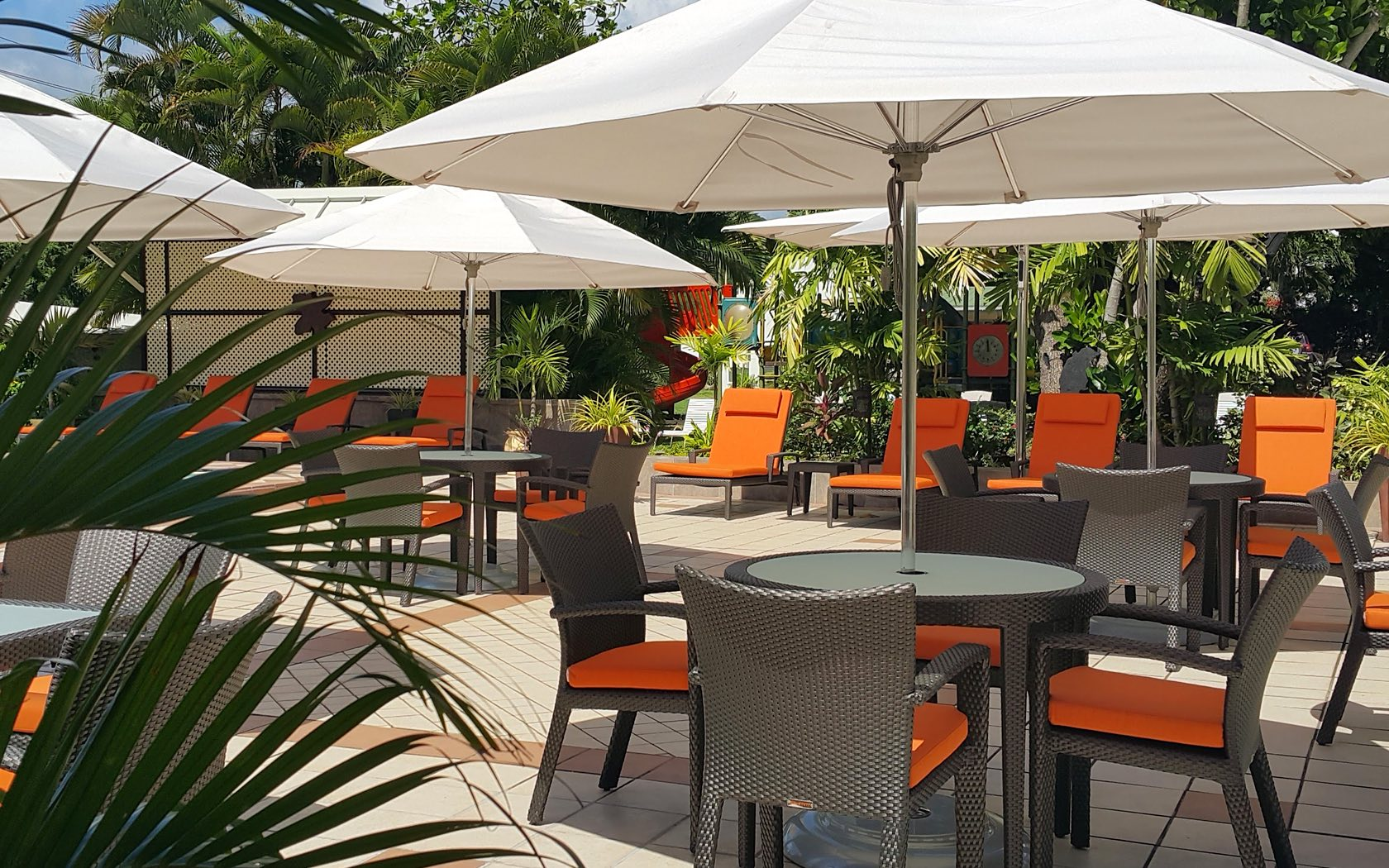 four person tables and chairs with orange cushions covered by white umbrellas with a line of orange cushioned lounge chairs behind the tables