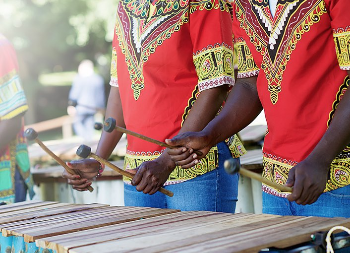 two men wearing red shirts with gold embroidery and blue jeans play a wooden xylophone