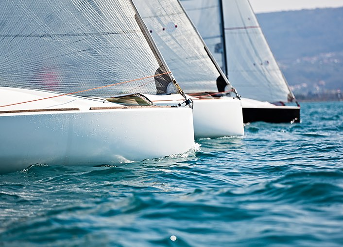 a close up of the front of three white sailboats in the water