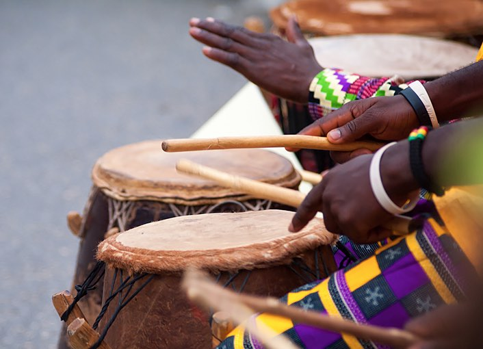 two people playing wooden drums with their hands and drum sticks