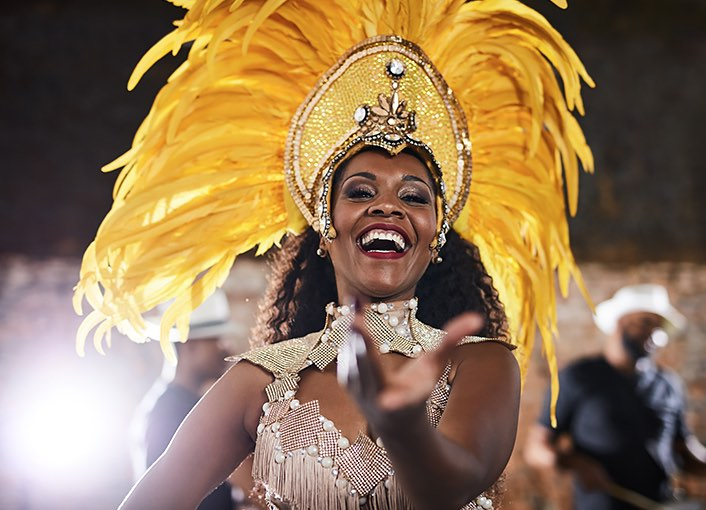 A woman wearing a large yellow feather headpiece at a night festival