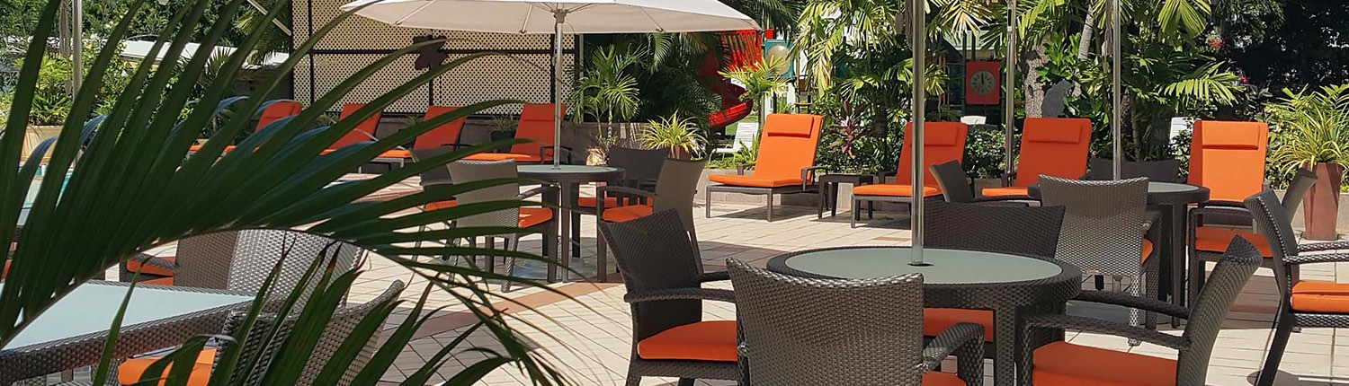 outdoor patio tables, chairs, and lounge chairs with orange cushions