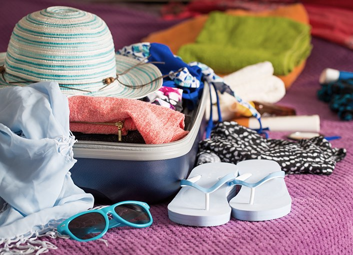 open suitcase filled with beach essentials sitting on a bed