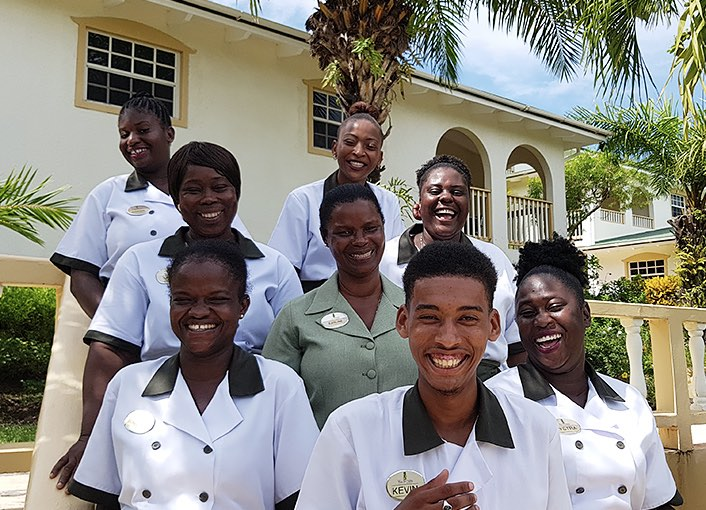 a group of hotel employees standing outside a building smiling together
