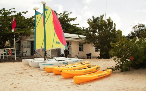 kayaks and small catamaran sailboats on the beach
