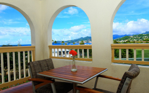a two person table with chairs on a covered outdoor porch with arched open windows and a view of the mountains and ocean in the distance