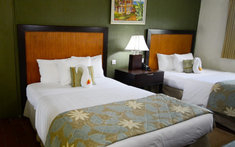 two guest beds with white linens and a green floral quilt