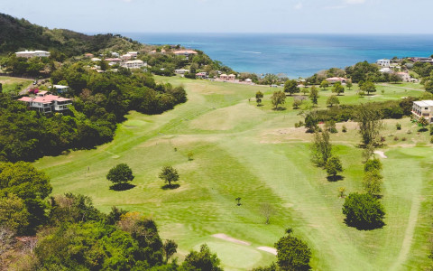 aerial view of a golf course green close to the ocean