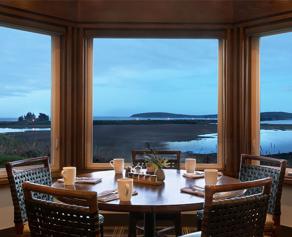 Round wooden dining table next to large window with ocean view