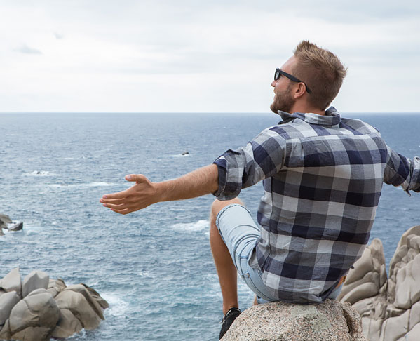 Man sitting on rock above the ocean with  arms spread out wide