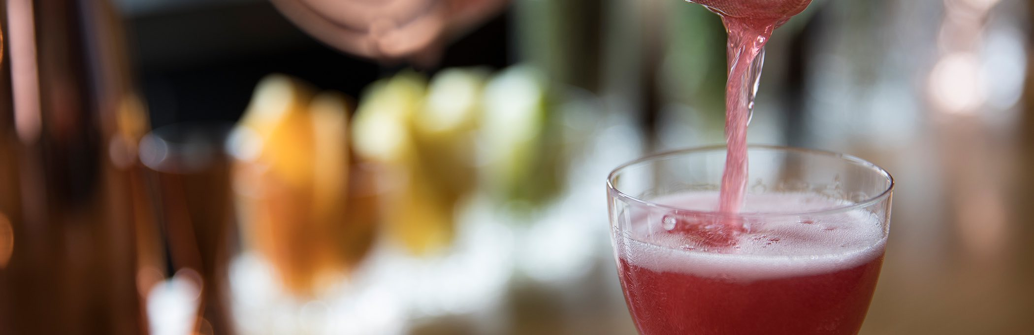 close up of a deep pink cocktail pouring from the shaker into a glass