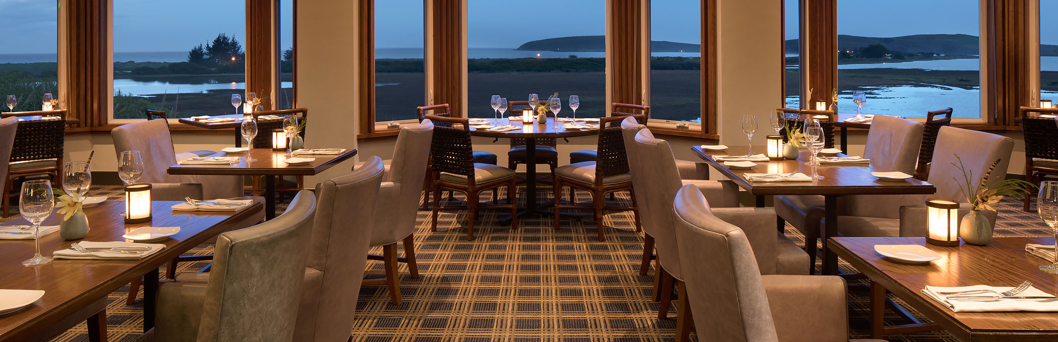 Drakes restaurant with wooden tables set for meal, sofa chairs & window panels with ocean view