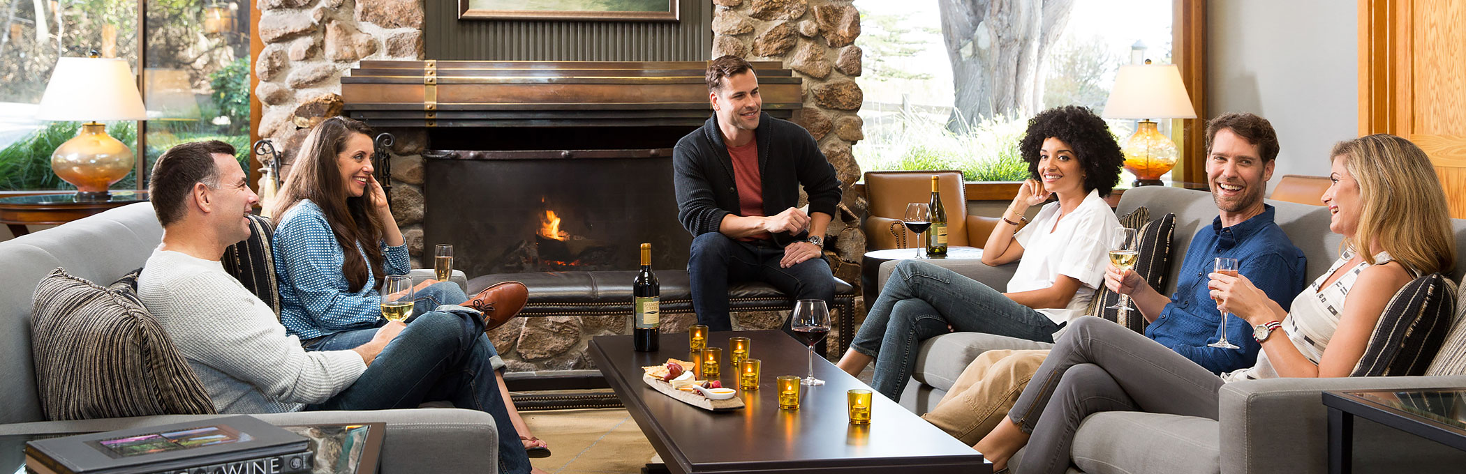 Group of friends gathered in living space drinking wine by fireplace