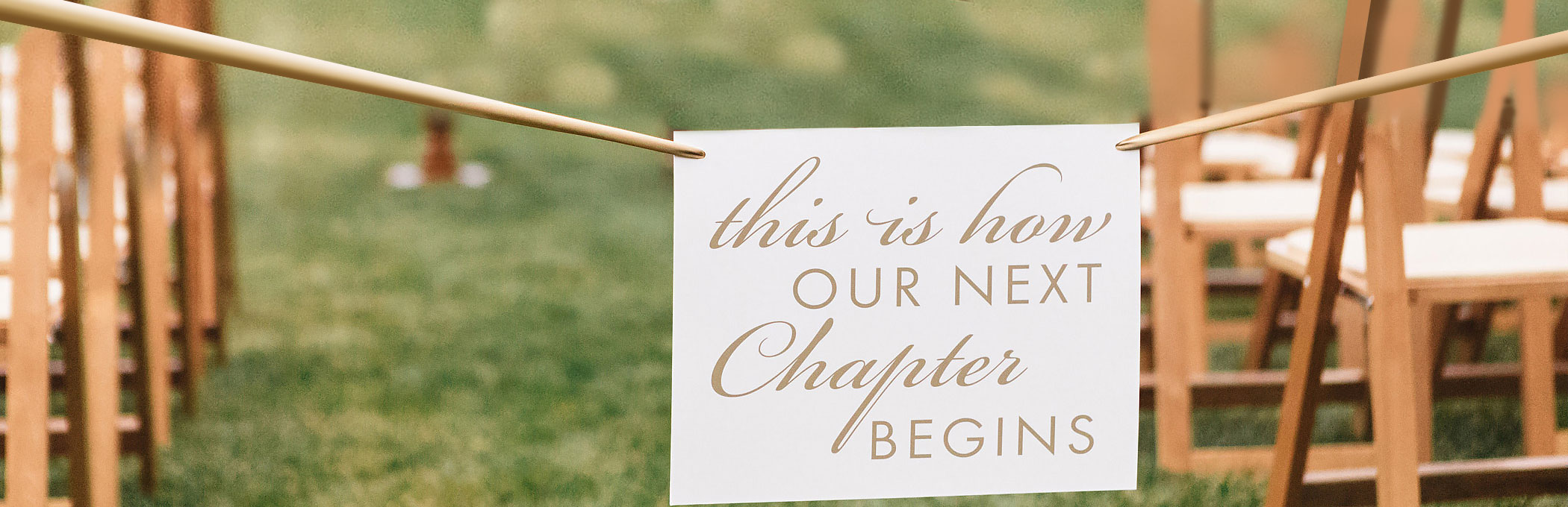 This is how our next chapter begins sign next to wedding ceremony chair set up