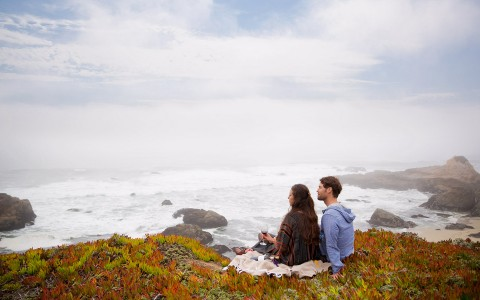 Couple sitting on a blanket having wine overlooking bodega head