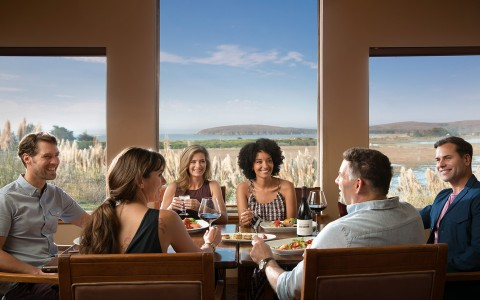 Group of friends gathered at dining table next to large window panels with view to the outdoors
