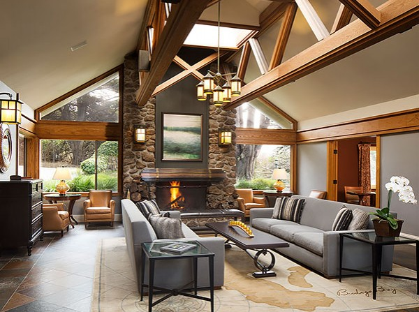 Warm living space with grey couches, black table, wooden architecture ceiling & fireplace