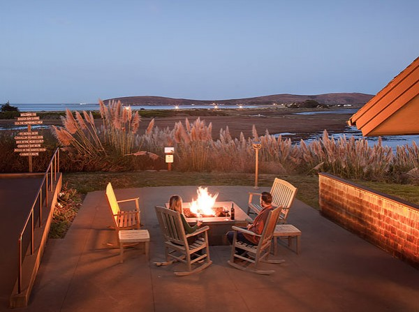 Outdoor seating area at night with fire pit lit up
