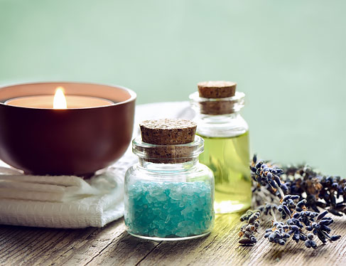 Aroma therapy rocks in bottles next to candle