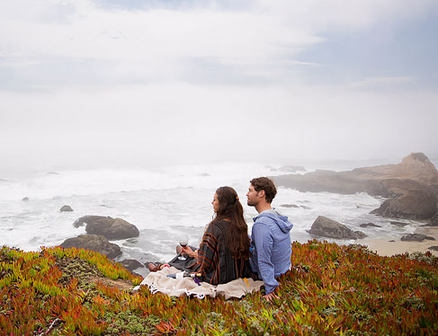 Couple sitting on grass on a blanket drinking wine at bodega head