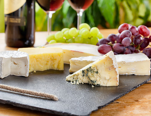 Variety of cheeses on plate next to grapes & wine