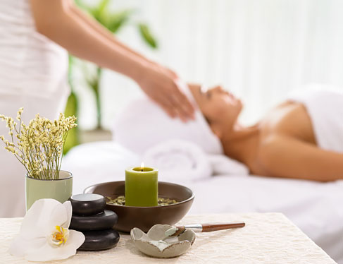 Focus on massage rocks, flowers & candle on table with woman getting facial in the back