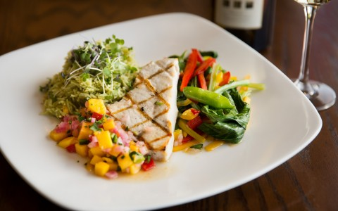 Plate with fresh fish, roasted vegetables and mango salsa