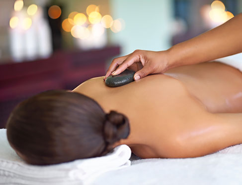 Woman laying down in spa with hot rock on back