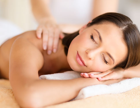Woman laying down with eyes closed getting massage