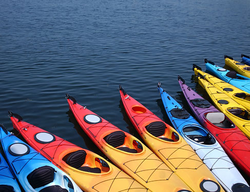 Row of colorful kayaks on the water