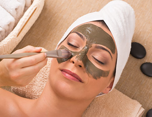 Woman at spa getting mud mask applied