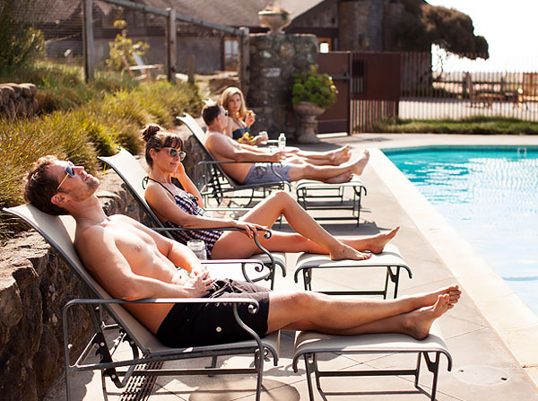 Group of people sun bathing by the pool